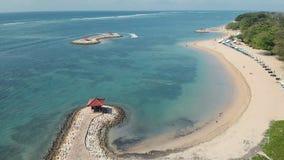 Metraggio aereo di bella spiaggia di Sanur e la città nei precedenti in Bali Indonesia archivi video