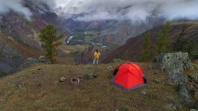 Metraggio aereo di un uomo che sta vicino ad una tenda davanti alla valle della montagna, 4K stock footage