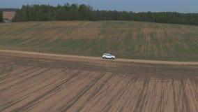 Metraggio aereo Giri bianchi dell'automobile sul campo stock footage