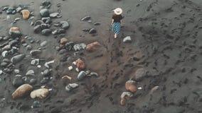 Metraggio aereo perfetto dall'isola di Tenerife - una giovane, ragazza alla moda vestita in un cappello, camminante lungo il nero archivi video