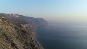 Metraggio aereo volante di bella vista della roccia e del mare enormi della montagna al tramonto video d archivio