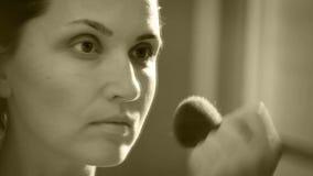 Metraggio in bianco e nero di seppia di giovane stendere il trucco attraente della donna video d archivio