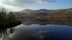 Metraggio del fuco del lago calmo e montagne contro il cielo stock footage