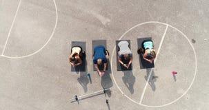 Metraggio del fuco e aereo del gruppo di uomini ben preparati e donne che fanno gli esercizi video d archivio