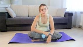 Metraggio del movimento lento della giovane donna esaurita che si siede sulla stuoia di forma fisica e che pulisce dopo sudore co archivi video