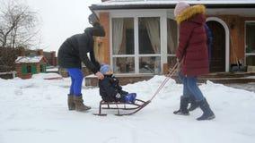 Metraggio del movimento lento della guida sorridente sveglia del neonato sulle slitte con la famiglia al cortile stock footage