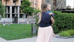 Metraggio del movimento lento di bella giovane donna che tiene suo figlio del bambino e che cammina al parco archivi video