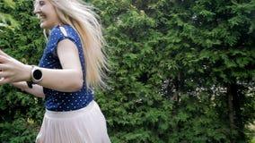 Metraggio del movimento lento di funzionamento felice della giovane donna al parco fra i cespugli e sorridere alla macchina fotog archivi video
