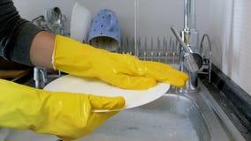 Metraggio del movimento lento del primo piano della casalinga in guanti di gomma gialli che lava i piatti nel lavandino di cucina video d archivio