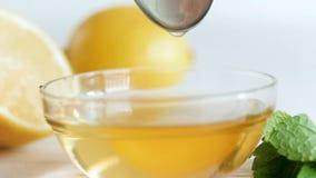 Metraggio del movimento lento del primo piano di miele che gocciola lentamente dal cucchiaio in barattolo di vetro sulla tavola d video d archivio