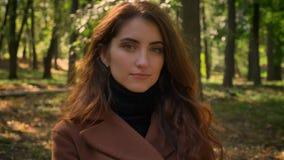 Metraggio del primo piano della femmina caucasica piacevole con capelli castana lunghi ed il sembrare aperto diritti nei sunlight video d archivio