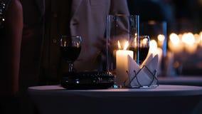 Metraggio del primo piano della tavola elegante decorata al ristorante, donna che tiene un vetro di vino rosso, borsa di frizione archivi video