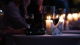 Metraggio del primo piano della tavola elegante decorata al ristorante, ospite femminile che tiene un vetro di vino rosso, il ner archivi video