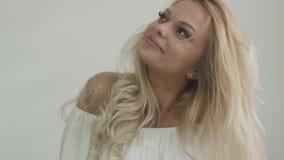 Metraggio del primo piano di una ragazza bionda attraente che posa nello studio con il fondo bianco della parete video d archivio