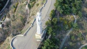 Metraggio dell'angolo alto della statua di Georgia della madre e di un vicolo con la gente che cammina, 4k archivi video
