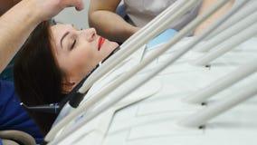 Metraggio della borsa degli arnesi del dentista sul primo paziente della sfuocatura e di piano che si siede sulla sedia del denti stock footage