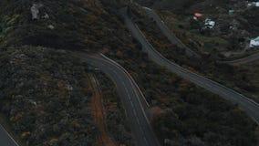 Metraggio della panoramica del fuco delle automobili su una strada tortuosa elevata stock footage