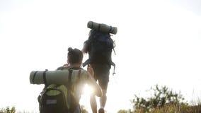 Metraggio della parte di giovane coppia che fa un'escursione insieme Scalata della cima della collina Felice, sorridendo, godendo stock footage
