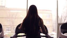 Metraggio della parte di un atleta femminile allegro con funzionamento castana lungo dei capelli sulla pedana mobile all'interno  video d archivio