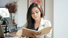 Metraggio di HD, bella lettura della donna di affari e vibrazione sopra la pagina del taccuino in caffè della caffetteria nella c stock footage