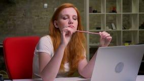 Metraggio di seduta caucasica della donna dello zenzero annoiato dell'interno nel suo luogo di lavoro vicino al computer portatil video d archivio