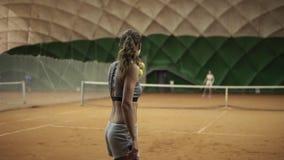 Metraggio di un grazioso, giovane donna del lato posteriore con la protesi della gamba che gioca a tennis con il rivale Servizio  video d archivio