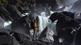 Metraggio di un turista che si avvicina ad un watertfall roccioso stock footage