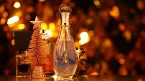 Metraggio di vetro del hd dell'albero di abete del bokeh dell'oro della bottiglia di profumo archivi video
