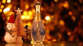 Metraggio di vetro del hd del pupazzo di neve dell'albero di abete del bokeh dell'oro della bottiglia di profumo archivi video