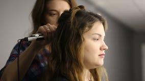 Metraggio, il processo di arricciatura dei capelli Parrucchiere e cliente closeup stock footage