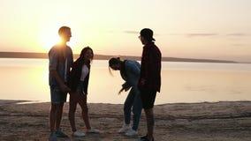 Metraggio integrale degli amici che vanno in giro o una spiaggia vicino all'acqua Conversazione, laughung, divertendosi Le risate stock footage