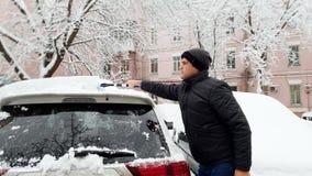 metraggio 4k del giovane che libera la sua automobile dalla neve dopo la bufera di neve con la spazzola telescopica video d archivio