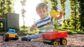 metraggio 4k del ragazzino che si siede sulla terra al parco e che gioca con i giocattoli di plastica archivi video