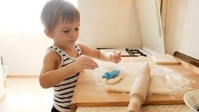 metraggio 4k del ragazzo adorabile del bambino che gioca con la pasta mentre producendo torta sulla cucina stock footage