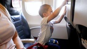 metraggio 4k del ragazzo sorridente adorabile del bambino che gioca con la tavola sul sedile del passeggero all'aeroplano video d archivio