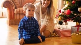 metraggio 4k del ragazzo sorridente adorabile del bambino che si siede con la madre sotto l'albero di Natale alla mattina video d archivio