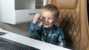 metraggio 4k del ragazzo sorridente adorabile del bambino che si siede nella sedia del grande capo all'ufficio ed agli occhiali d stock footage