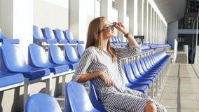metraggio 4k di bella giovane donna in occhiali da sole che si rilassano sul posto vuoto allo stadio video d archivio