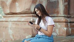 metraggio 4k di bella ragazza sorridente che si siede sulla scala di pietra sulla via e che per mezzo dello smartphone stock footage