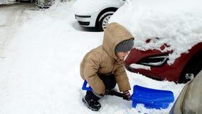 metraggio 4k di piccoli 3 anni del bambino della neve di scavatura del ragazzo su parcheggio dell'automobile con la pala video d archivio