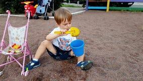 metraggio 4k di poca sabbia di scavatura del ragazzo del bambino con il mestolo ed il versamento in secchio di plastica del gioca stock footage