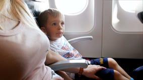 metraggio 4k di poco ragazzo del bambino che esamina nervoso madre durante l'aeroplano che decolla la terra stock footage
