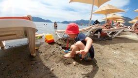 metraggio 4k di sorridere adorabile 2 anni del ragazzo che gioca con la sabbia sulla spiaggia in mare stock footage