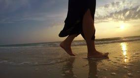 metraggio 4K di una donna che cammina lungo il litorale al tramonto video d archivio