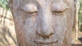 metraggio 4k Fronte calmo e pacifico di vecchia testa della statua di Buddha di culto illuminata Statua di Buddha al tempio di st video d archivio