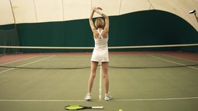 Metraggio lento della parte di giovane tennis femminile allegro con gli abiti sportivi bianchi d'uso dei brevi capelli biondi stock footage