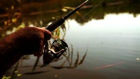 Metraggio lento di una barretta di filatura nelle mani di un pescatore dilettante stock footage