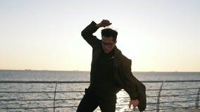Metraggio potato di giovane, ballerino maschio alla moda che esegue stile libero dello schiocco dell'anca, condizione di danza mo video d archivio