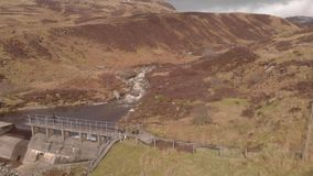 Metraggio a rovescio aereo di una diga della montagna nella montagna scozzese archivi video