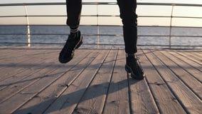 Metraggio teso delle gambe maschii nel ballare Il hip-hop moderno ha eseguito dall'uomo in scarpe da tennis nere con un mare di m video d archivio